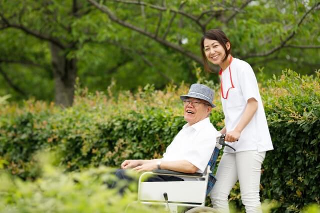 介護士と高齢者の散歩